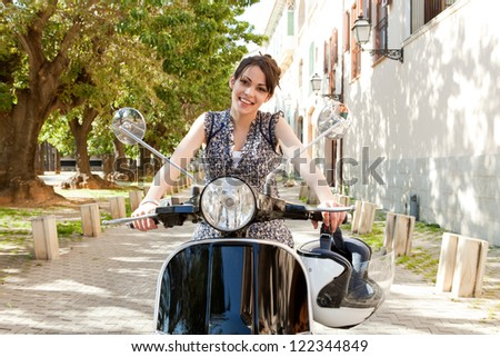 Young woman sitting on a classic motorbike while visiting a small city destination on vacations, with charming buildings and aligned trees behind her. - stock photo