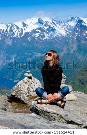 Young woman sitting on a cliff and enjoy the view - stock photo