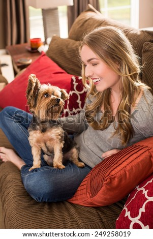 Young woman sitting on a couch with her dog - stock photo
