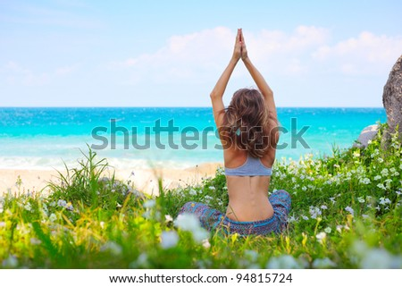 Young woman sitting on a green meadow near a beach and stretching