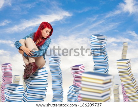 young woman sitting on a high books pile