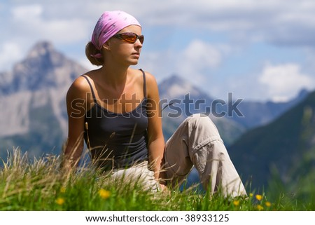 Young woman sitting on a high hill. Mountain region in Austria. Alps - stock photo