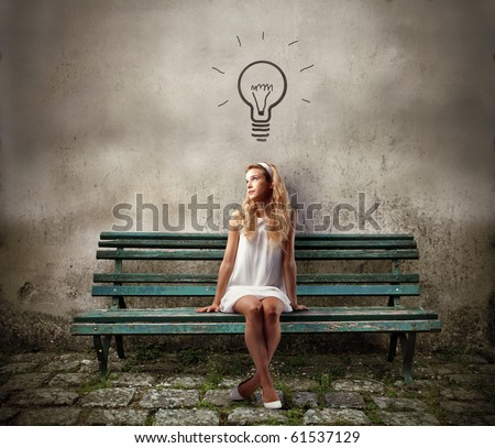 Young woman sitting on a park bench and having an idea - stock photo