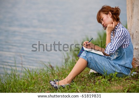 Young woman sitting on a park bench and having an idea.