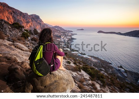 Young woman sitting on a rock and watching sunset - stock photo