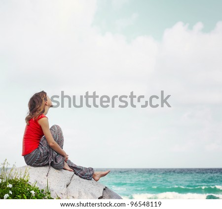 Young woman sitting on a rock near a beach and looking to a sky - stock photo