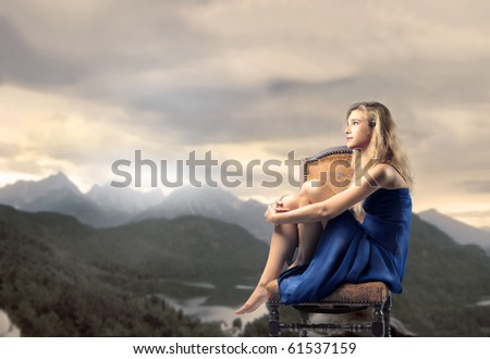 Young woman sitting on a rock with mountains at dawn on the background