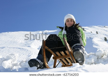 Young woman sitting on a sled in snow - stock photo