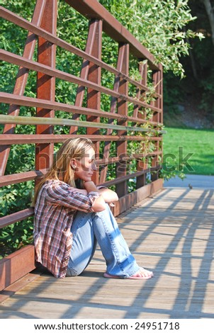 Young woman sitting on a small bridge thinking and looking at the sun. - stock photo