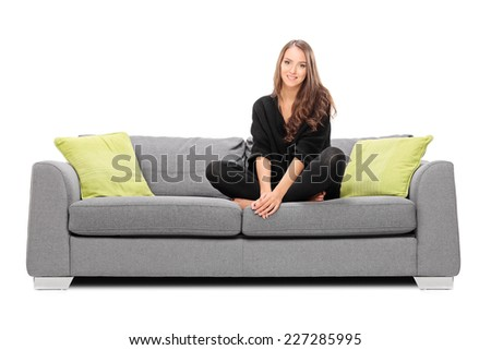 Young woman sitting on a sofa and looking in the camera isolated on white background - stock photo