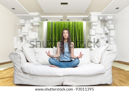 Young woman sitting on a sofa in the lotus position meditating in a zen environment - stock photo