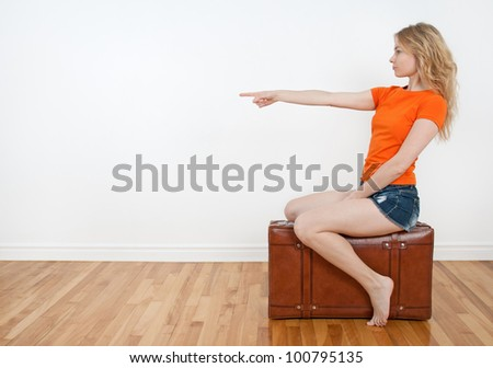 Young woman sitting on a suitcase and pointing direction where to go. - stock photo