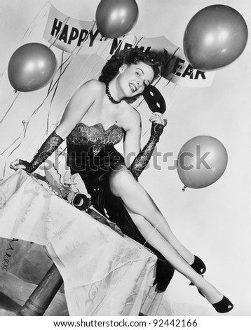 Young woman sitting on a table with balloons and sign - stock photo