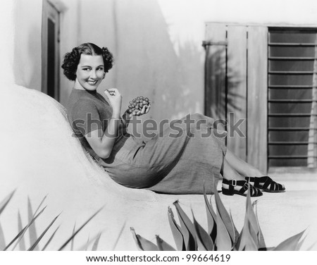 Young woman sitting on a terrace smiling and eating grapes