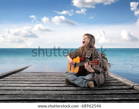 Young woman sitting on a wharf and singing and playing guitar - stock photo
