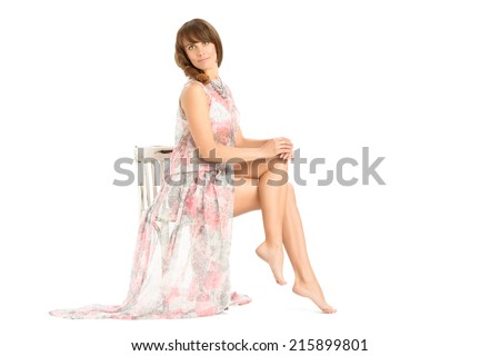 Young woman sitting on a white vintage shabby chair and looking at camera, legs crossed.