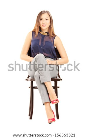 Young woman sitting on a wooden chair isolated on white background