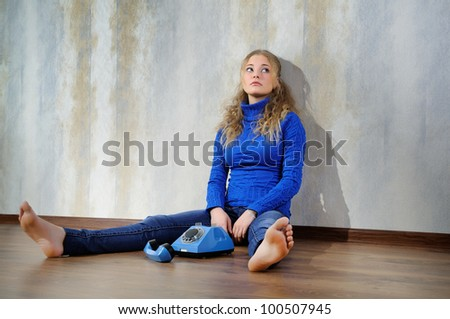Young woman sitting on a wooden floor with old phone.