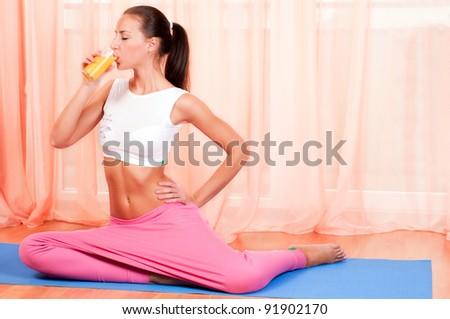 Young woman sitting on a yoga mat drinking orange juice - stock photo