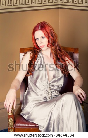Young woman sitting on an old chair - stock photo