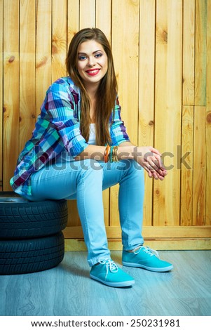 Young woman sitting on auto tires against wooden wall. Smiling model with long hair. Beautiful girl portrait. - stock photo
