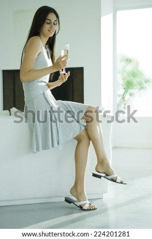 Young woman sitting on back of sofa, holding glass of champagne, full length - stock photo