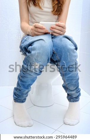 Young  woman sitting on bathroom or wc toilet bowl using phone in hands . - stock photo
