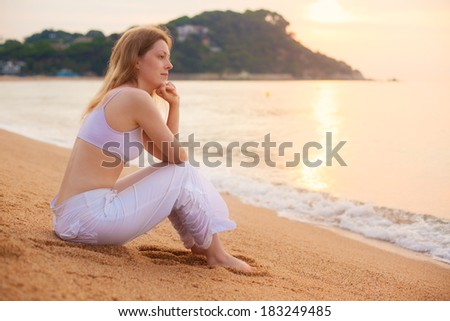 Young woman sitting on beach at morning. - stock photo