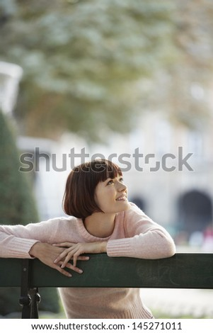 Young woman sitting on bench in front of blurred fountain - stock photo