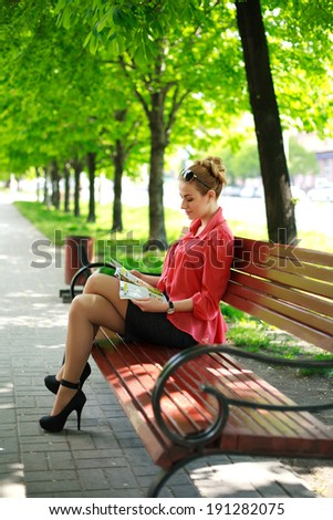 Young woman sitting on bench in green park, reading magazine - stock photo
