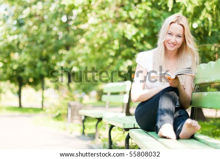 young woman sitting on bench in park, reading book, smiling and looking into the camera - stock photo