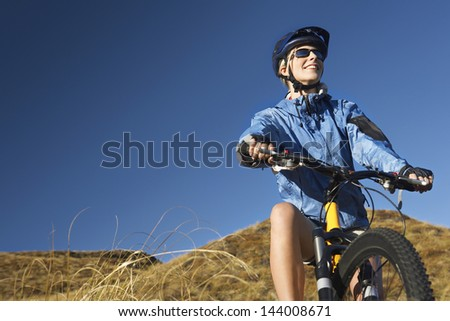 Young woman sitting on bicycle in field against clear blue sky - stock photo