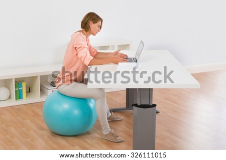 Young Woman Sitting On Blue Fitness Ball Using Laptop At Desk - stock photo