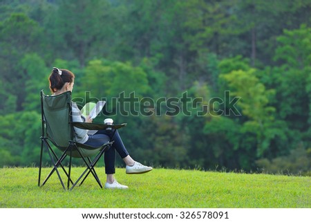 Young woman sitting on camping chair reading a book in the park  - stock photo