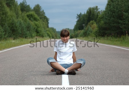 Young woman sitting on center mall of the road - stock photo
