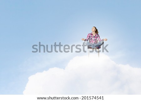 Young woman sitting on chair and meditating - stock photo