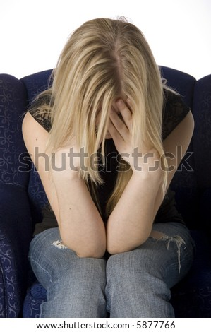Young woman sitting on chair in a depressed state - stock photo