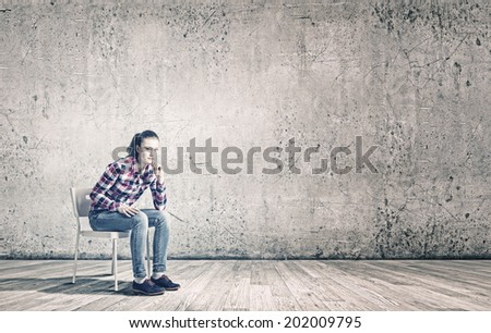 Young woman sitting on chair in empty room - stock photo