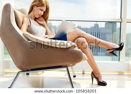 Young woman sitting on chair with laptop. - stock photo