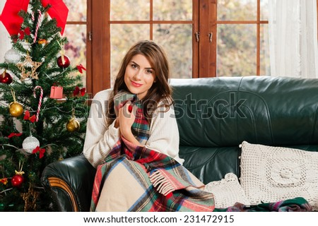 Young woman sitting on couch, alone, holding a blanket ,over christmas tree background on living room - stock photo