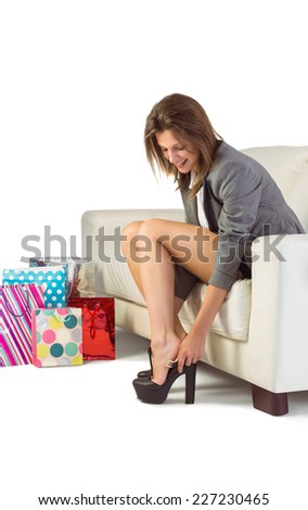Young woman sitting on couch taking off her shoes at home in the living room - stock photo