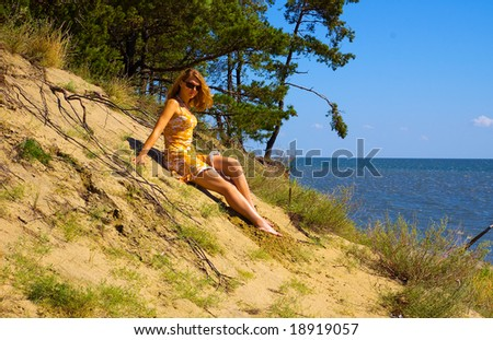 Young woman sitting on dune in the forest - stock photo