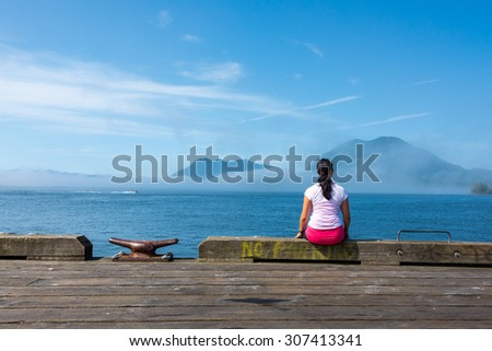 Young woman sitting on edge of dock in Tofino, British Columbia, looking out to the ocean with islands & fog surrounding them. - stock photo