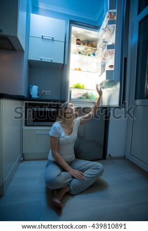 Young woman sitting on floor and reaching for food from open refrigerator at late night - stock photo