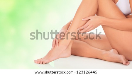 Young woman sitting on floor, green blurred background - stock photo