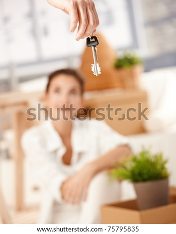 Young woman sitting on floor, man hanging keys of new house in foreground.? - stock photo