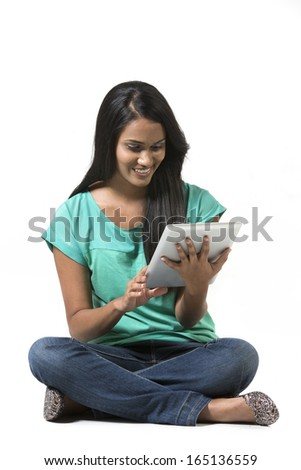 Young woman sitting on floor using a Digital Tablet PC. Isolated on white background. - stock photo