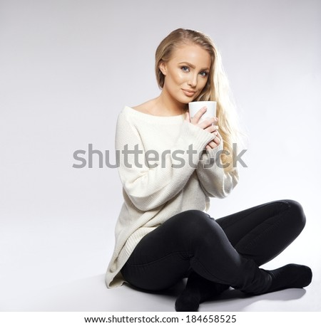 Young woman sitting on floor with cop of coffee or tea. Isolated shot with copy space left. - stock photo
