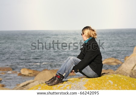 Young woman sitting on granite rock in brittany, watching the atlantic ocean. - stock photo