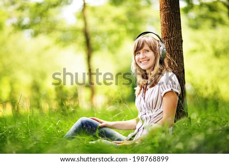 Young woman sitting on grass near a tree and listening to the music using big headphones.  - stock photo